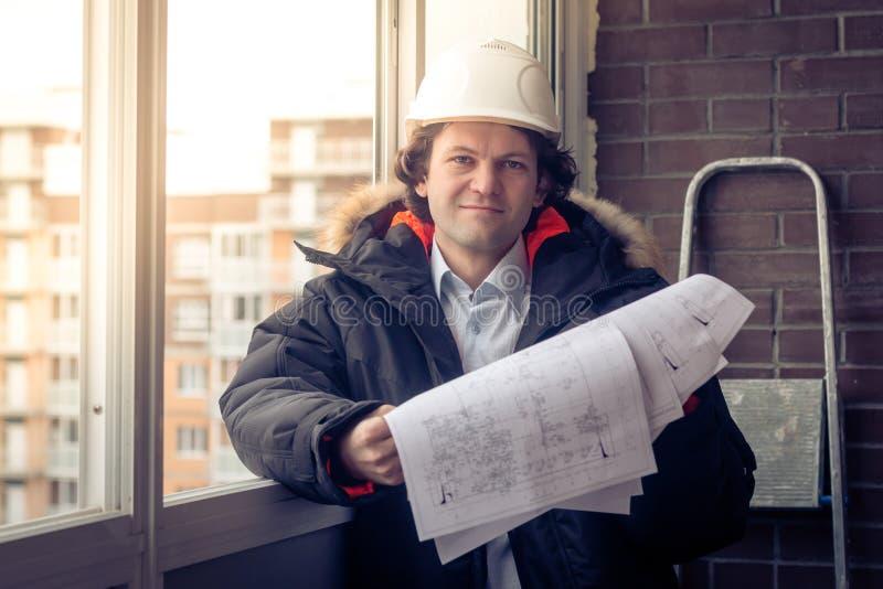 Ingeniero de construcción en el casco de protección con proyecto en manos Foco suave, entonado foto de archivo libre de regalías