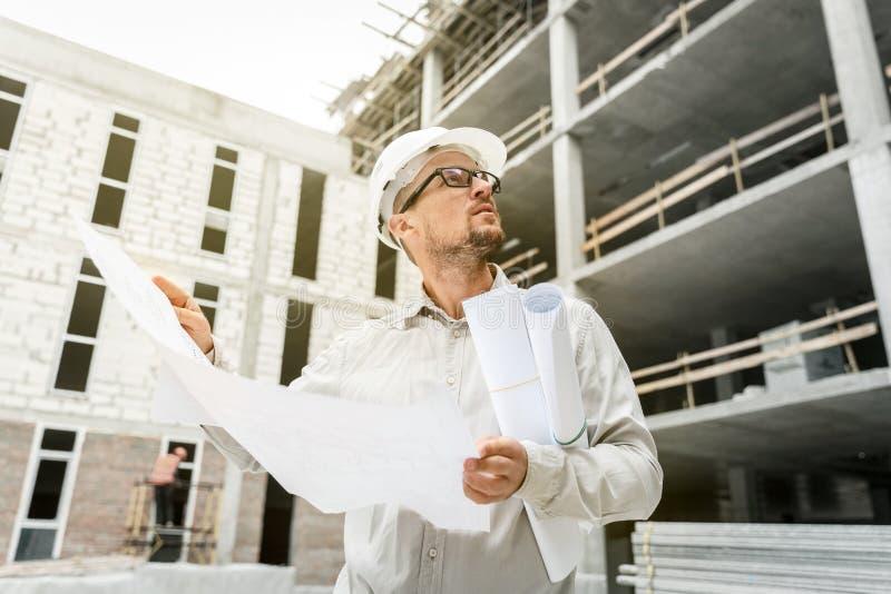 Ingeniero de construcción en un casco de protección blanco que examina los modelos o fotos de archivo
