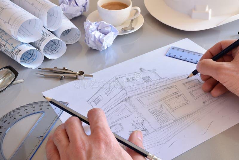 Ingeniero de construcción que dibuja una casa en su escritorio de oficina fotografía de archivo libre de regalías