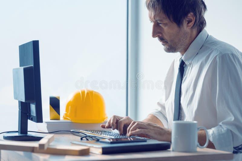 Ingeniero de construcción que trabaja en el equipo de escritorio usando el cad suavemente imagenes de archivo