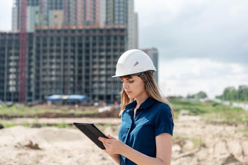 Ingeniero de construcción de sexo femenino Arquitecto con una tableta en un emplazamiento de la obra Mirada de la mujer joven, co imagen de archivo