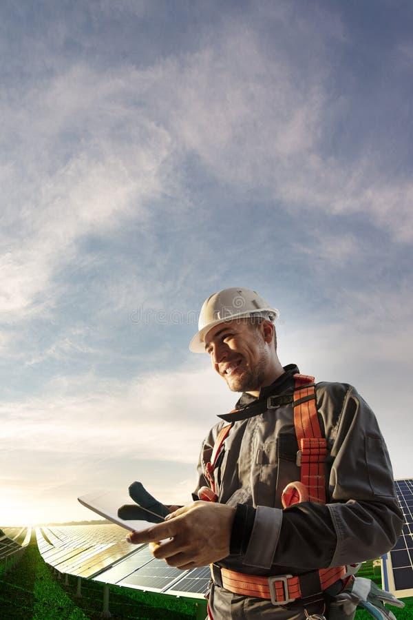 Ingeniero de energía solar usando la tableta para la sonrisa de la central eléctrica del control imagen de archivo
