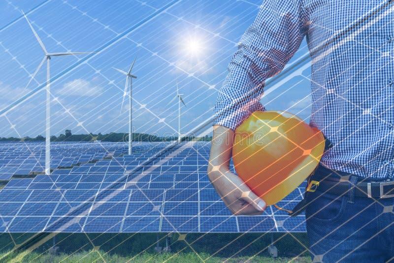 Ingeniero de la exposición doble que sostiene el casco amarillo en la estación de la energía solar con las turbinas de viento y l fotografía de archivo libre de regalías