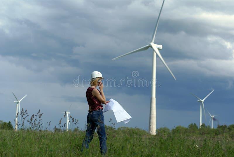 Ingeniero de la mujer con la turbina de viento blanca del sombrero de seguridad foto de archivo