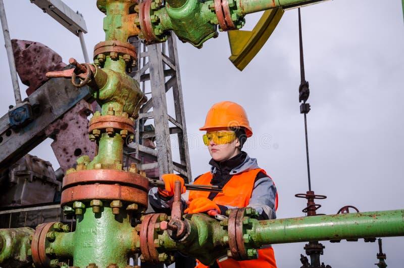 Ingeniero de la mujer en el campo petrolífero que repara el manantial fotos de archivo