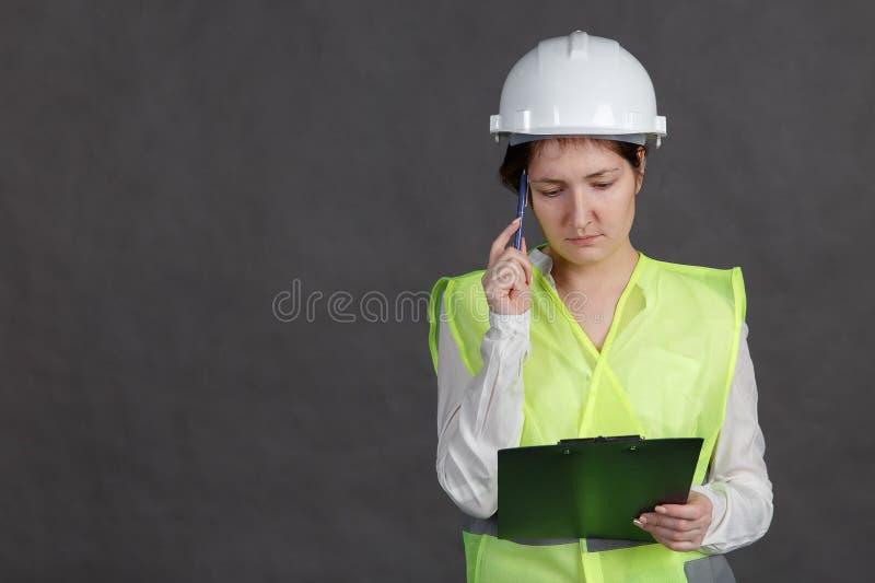 Ingeniero de la mujer joven en casco protector y chaleco con la pluma y tableta en manos Piensa sobre la idea fotos de archivo libres de regalías