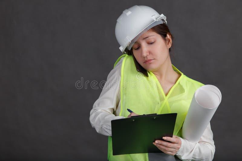 Ingeniero de la mujer joven en casco protector y chaleco que hablan en el teléfono y que toman notas foto de archivo