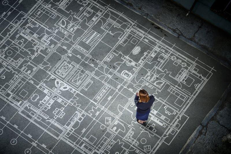 Ingeniero de la mujer que piensa sobre su plan Técnicas mixtas imagen de archivo
