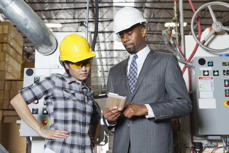 Ingeniero de sexo femenino del trabajador industrial y del varón en la discusión en la fábrica de la madera fotografía de archivo