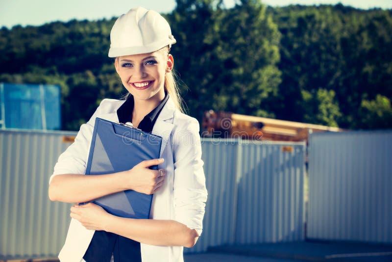 Ingeniero de sexo femenino en casco delante del emplazamiento de la obra imágenes de archivo libres de regalías