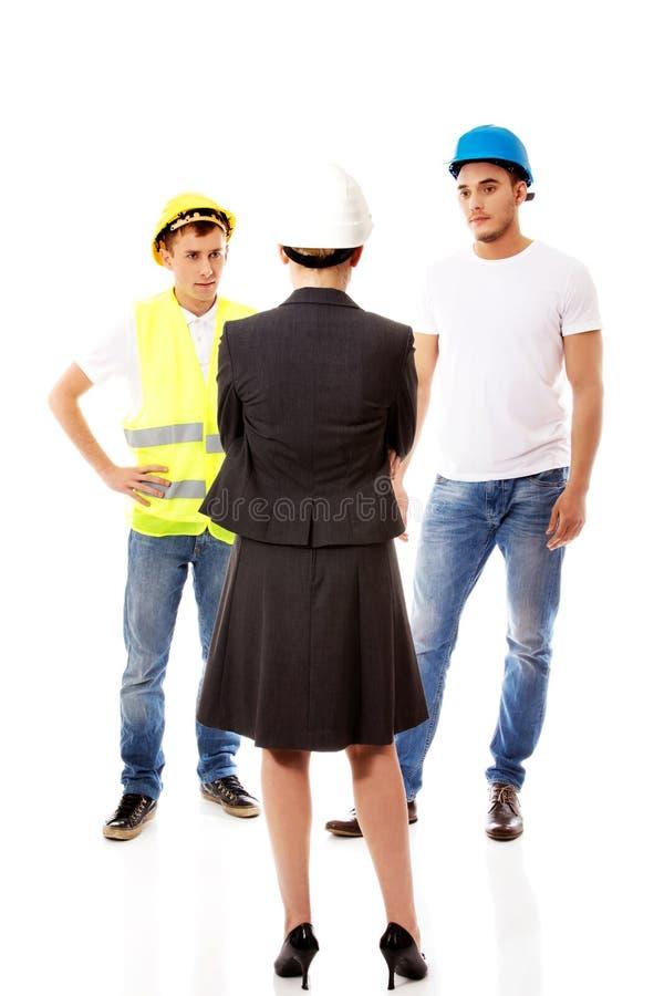 Ingeniero de sexo femenino que habla con dos constructores foto de archivo