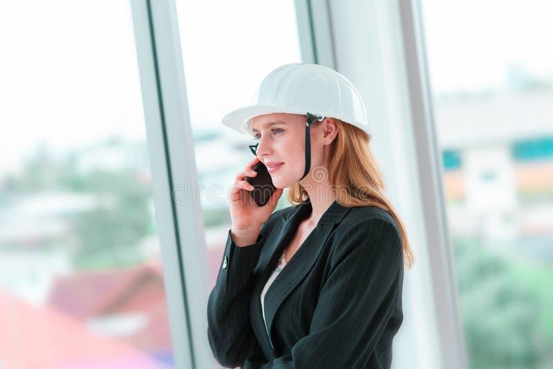 Ingeniero de sexo femenino que hace llamada en el edificio de oficinas imagen de archivo libre de regalías