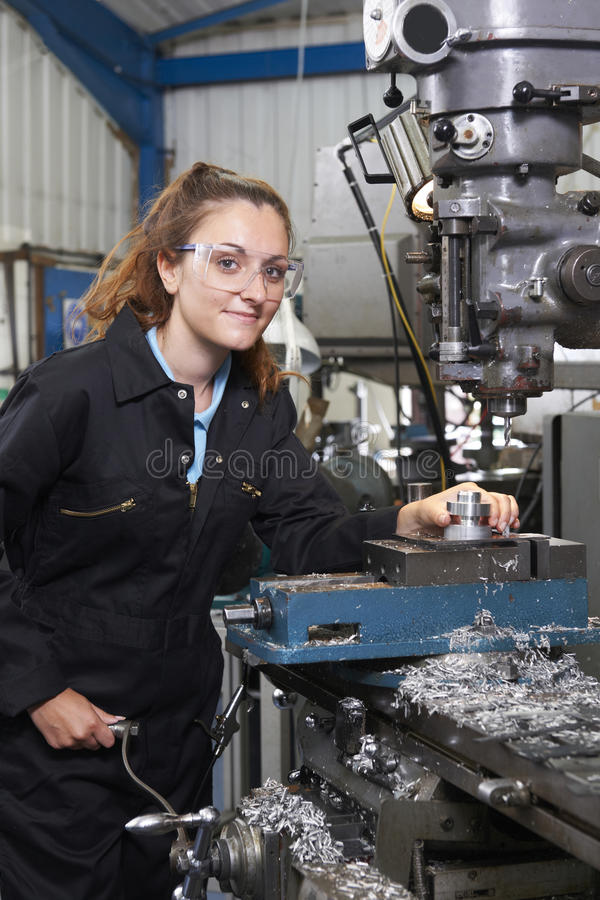 Ingeniero de sexo femenino Working On Drill del aprendiz en fábrica fotos de archivo