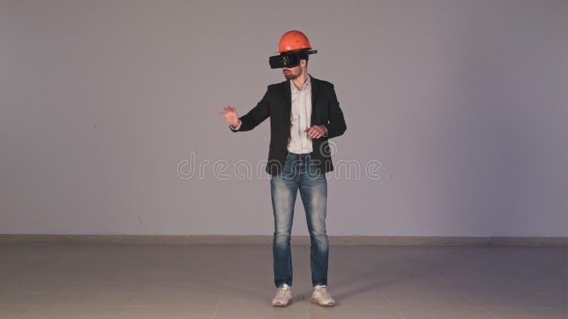 Ingeniero de sexo masculino joven en el casco de protección con los vidrios de VR que diseña proyecto de construcción fotos de archivo