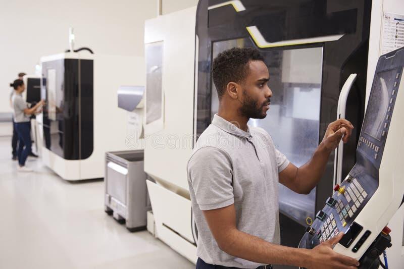 Ingeniero de sexo masculino que actúa la maquinaria del CNC en fábrica imagen de archivo