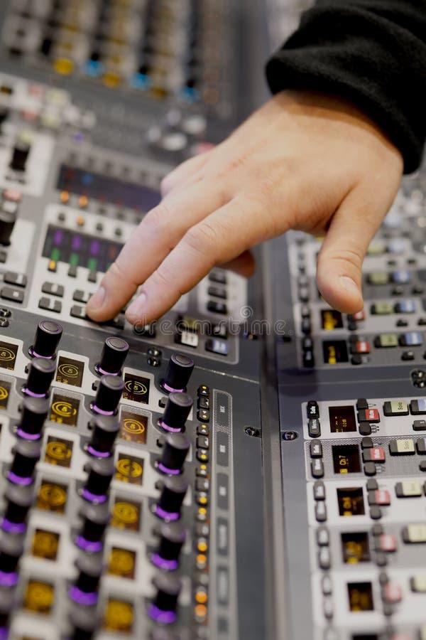 Ingeniero de sonido que trabaja en la consola del mezclador de la música imagen de archivo