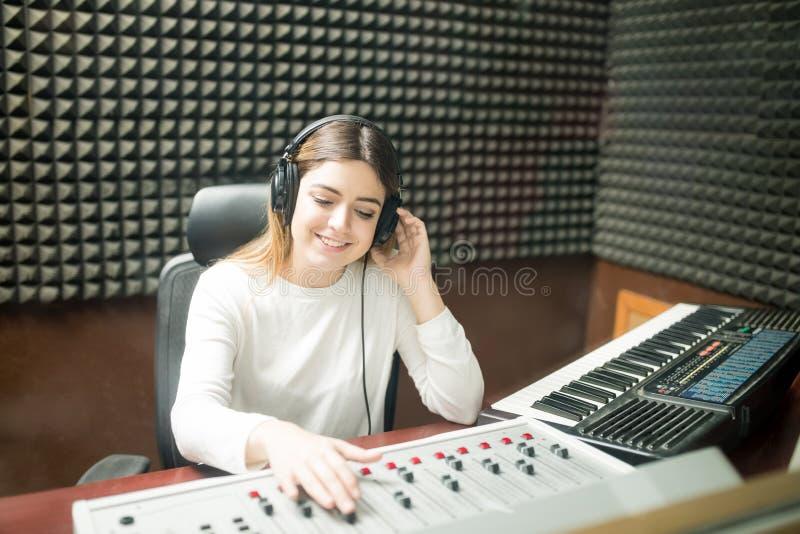 Ingeniero de sonido de sexo femenino que trabaja en el estudio de grabación foto de archivo