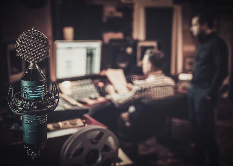 Ingeniero de sonido y productor que trabajan junto en el panel de mezcla en el estudio de grabación del boutique foto de archivo