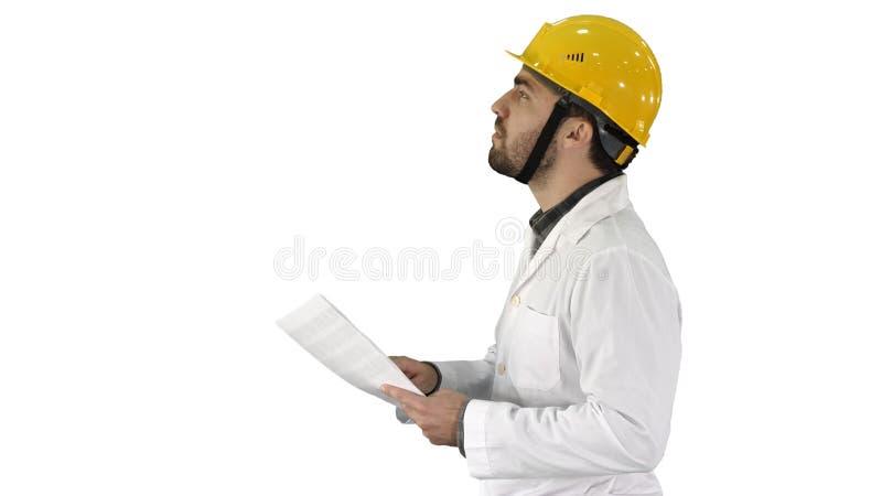 Ingeniero del contratista que camina con los papeles y que comprueba el arround en el fondo blanco fotografía de archivo libre de regalías