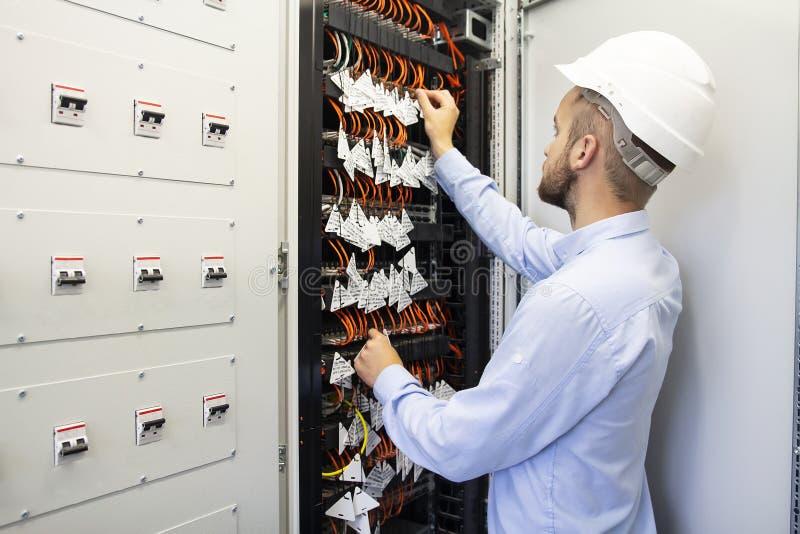 Ingeniero del técnico en datacenter Fibra óptica de conexión del técnico de la red en el sitio del servidor imagen de archivo libre de regalías
