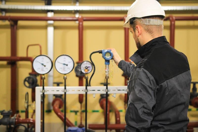 Ingeniero del técnico que comprueba los manómetros de los sensores de la presión y los datos de supervisión sobre la estación ind foto de archivo