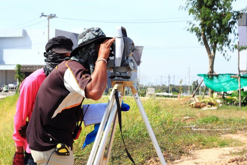 Ingeniero del topógrafo que hace la medición fotos de archivo
