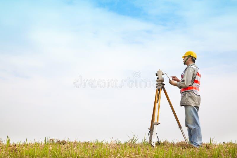 Ingeniero del topógrafo que hace medida con PC de la tableta fotos de archivo
