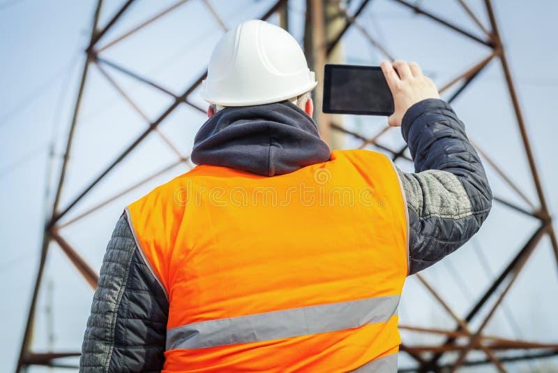 Ingeniero eléctrico filmado con la torre del alto voltaje de la tableta fotos de archivo