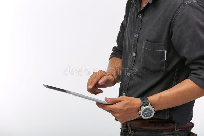 Ingeniero elegante del hombre joven que usa la tableta en la parte posterior aislada del blanco imagen de archivo
