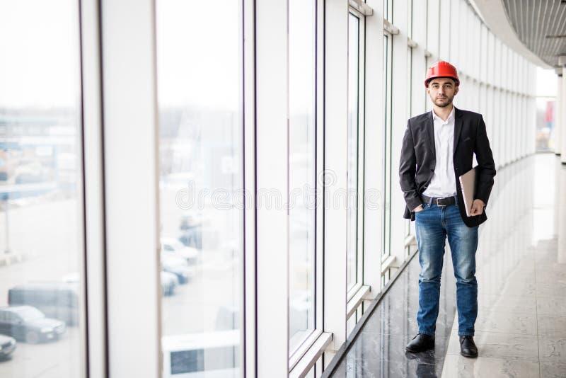 Ingeniero en el casco de protección con el ordenador portátil, sonriendo en la cámara fotografía de archivo