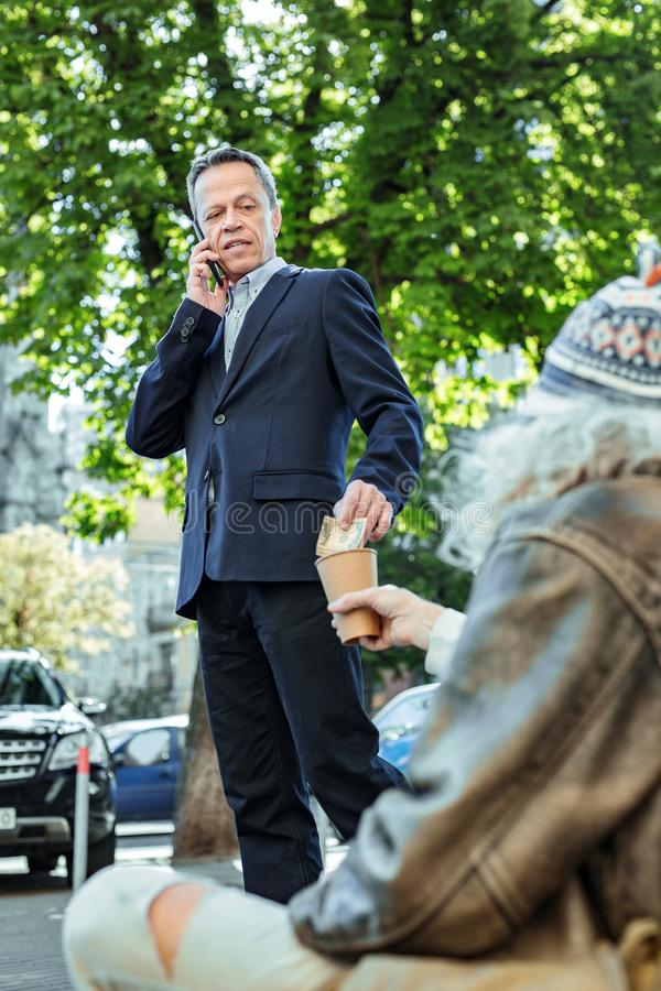 Ingeniero en el traje negro que da un poco de dinero a la persona de calle foto de archivo libre de regalías