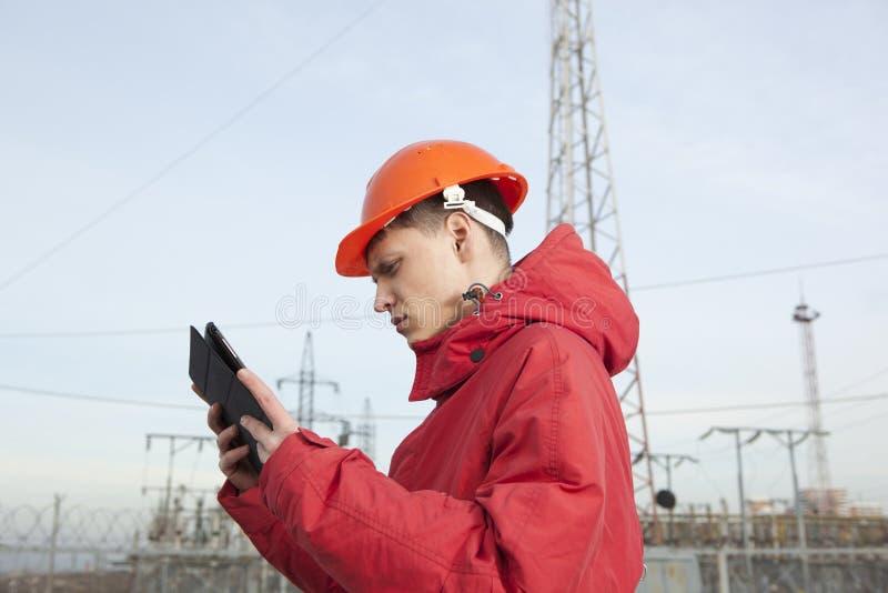 Ingeniero en la subestación eléctrica usando una tableta fotos de archivo libres de regalías