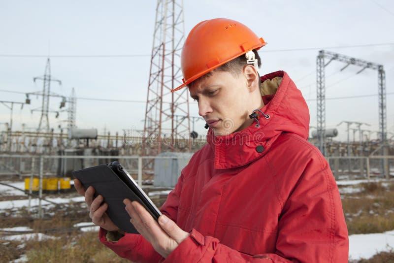 Ingeniero en la subestación eléctrica usando una tableta imagen de archivo