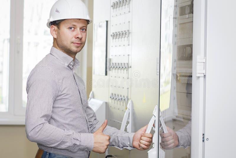 Ingeniero en sitio de panel de control  Trabajador en el casco blanco en la estación industrial de la tecnología Ingeniero en un  imagen de archivo libre de regalías