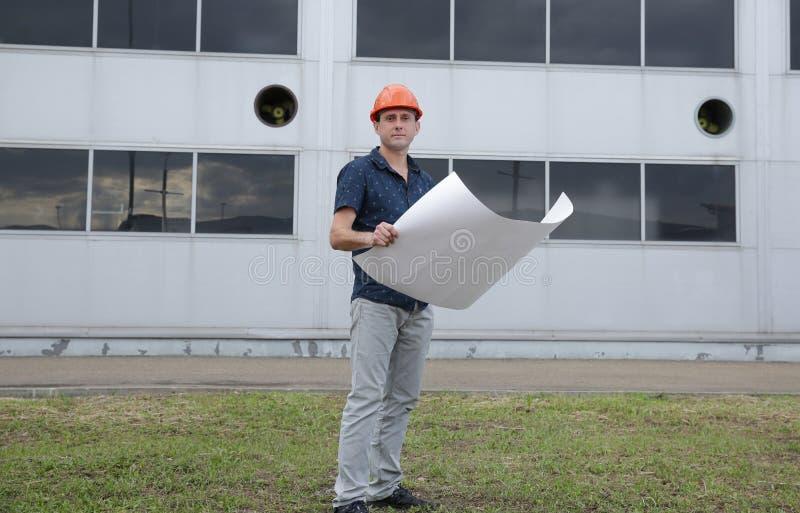 Ingeniero en un casco protector con los modelos delante del edificio foto de archivo