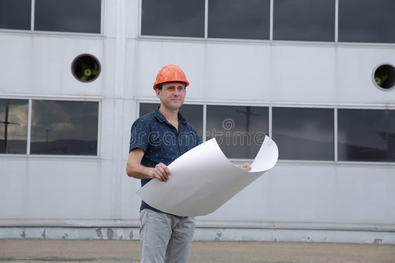 Ingeniero en un casco protector con los modelos delante del edificio fotos de archivo libres de regalías