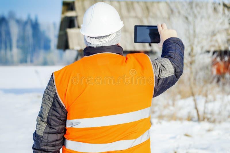 Ingeniero filmado con el edificio destruido tableta imagen de archivo libre de regalías