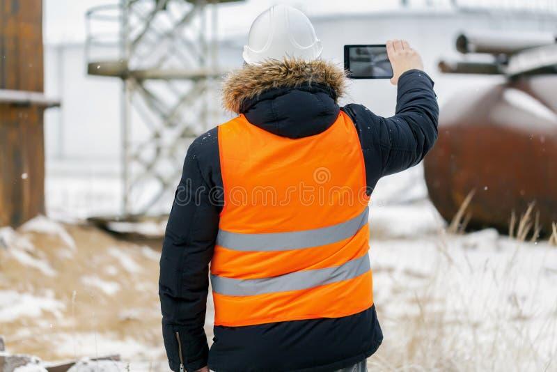 Ingeniero filmado con la tableta en la fábrica en invierno fotos de archivo