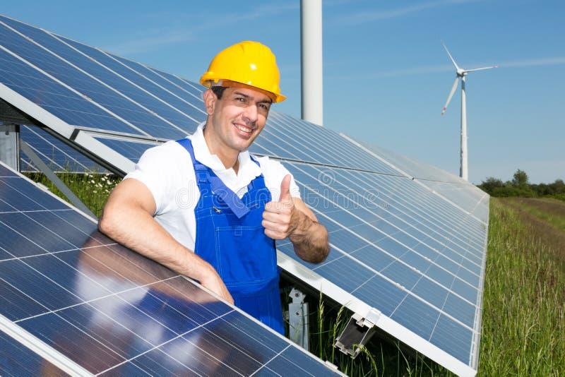 Ingeniero fotovoltaico que muestra los pulgares para arriba en el arsenal del panel solar imagen de archivo