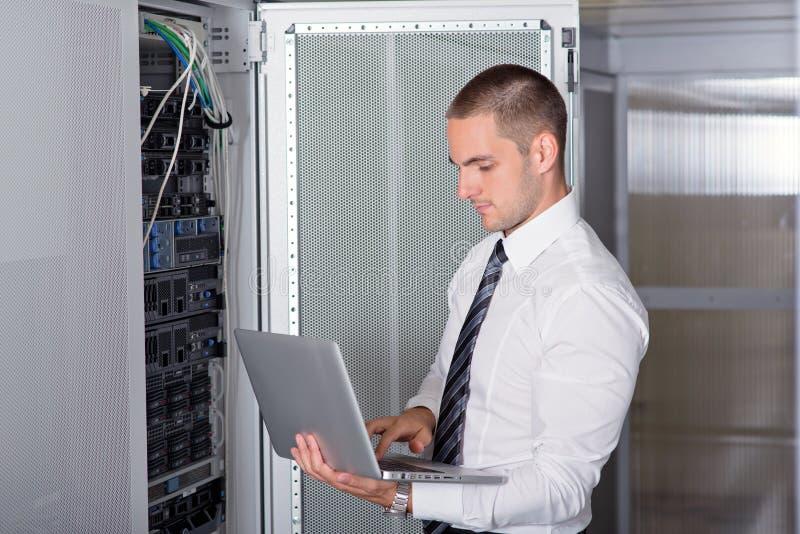 Ingeniero hermoso joven del hombre de negocios en sitio del servidor del datacenter imagenes de archivo