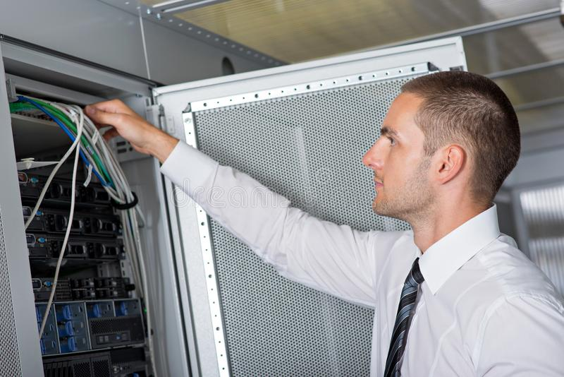 Ingeniero hermoso joven del hombre de negocios en sitio del servidor del datacenter foto de archivo