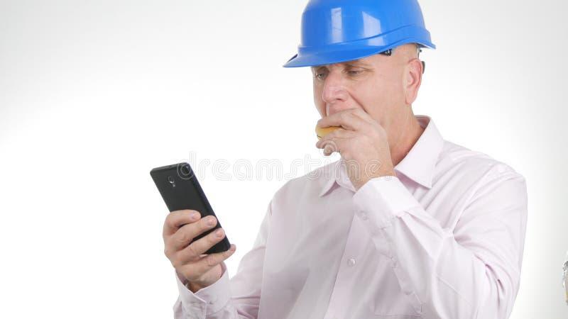 Ingeniero Image Eating un bocadillo y un texto usando el teléfono móvil imagen de archivo
