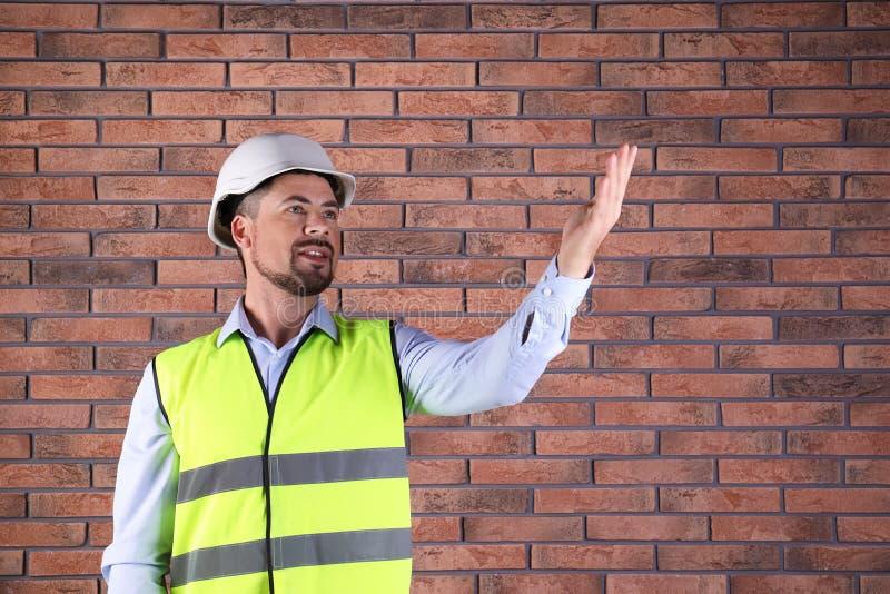 Ingeniero industrial de sexo masculino en uniforme en el fondo de la pared de ladrillo, espacio para el texto imagen de archivo