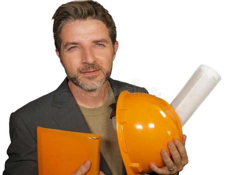 Ingeniero industrial joven o arquitecto atractivo y acertado en el casco del constructor de la seguridad que sostiene el modelo d fotos de archivo