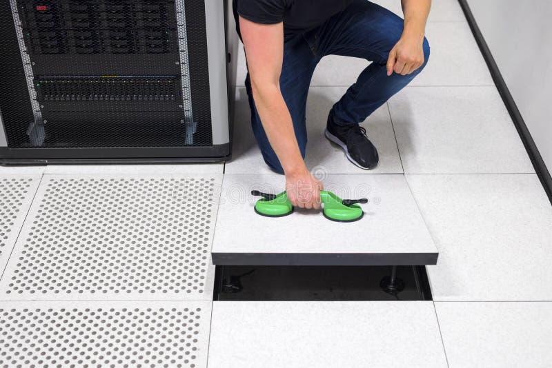 Ingeniero informático Pulling Floor Tile que usa las ventosas en Datac foto de archivo libre de regalías