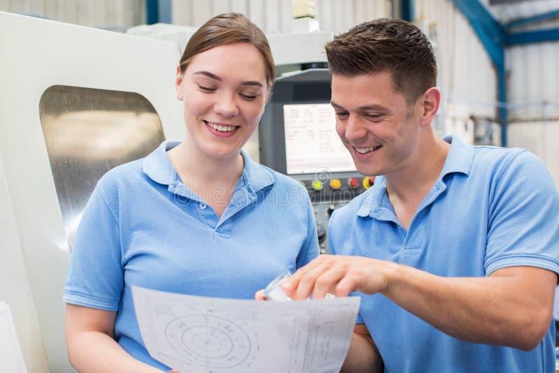 Ingeniero Instructing Female Apprentice en el uso de la máquina del CNC fotografía de archivo libre de regalías