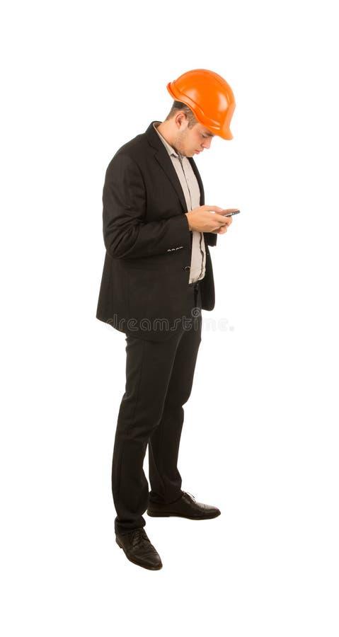 Ingeniero joven que usa su teléfono móvil para mandar un SMS fotos de archivo
