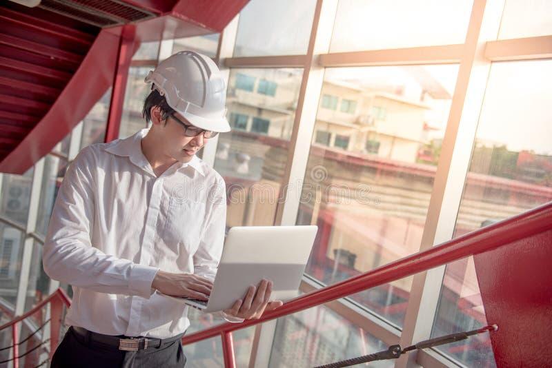 Ingeniero o arquitecto asiático joven que trabaja con el ordenador portátil fotografía de archivo