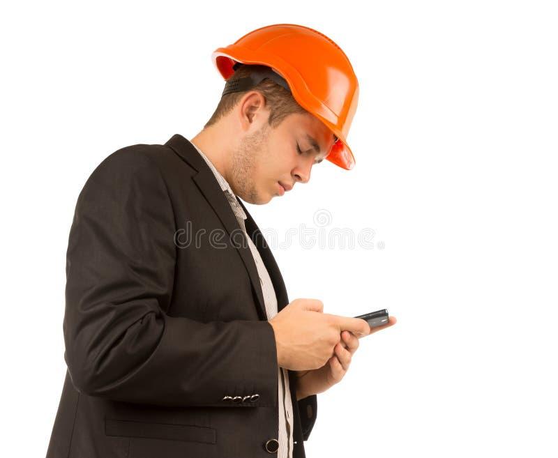 Ingeniero o arquitecto joven que lee un mensaje de texto foto de archivo libre de regalías