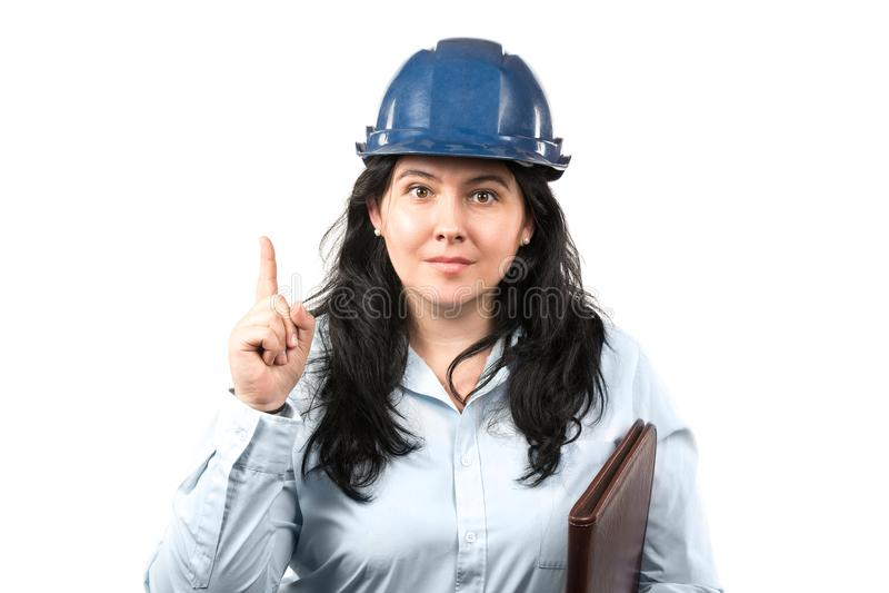 Ingeniero o arquitecto moreno atractivo joven de la mujer con el finger azul del indicador de la demostración del sombrero de seg fotografía de archivo